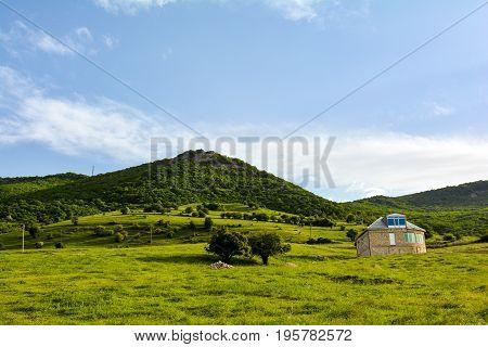 Tilted house on the mountainside. Summer green landscape