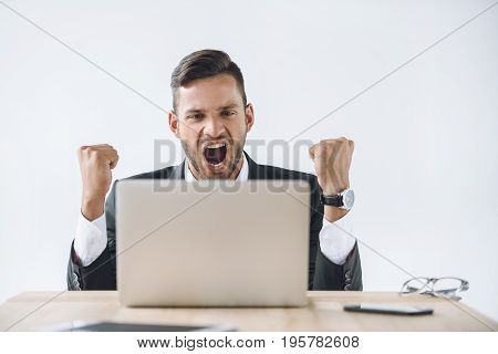Portrait Of Excited Businessman Looking At Laptop Screen At Workplace Isolated On White