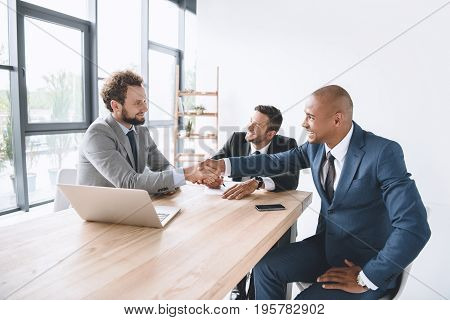 Multiethnic Smiling Businessmen Shaking Hands At Meeting At Workplace With Laptop
