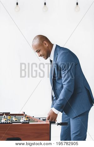 Side View Of Focused Businessman In Suit Playing Table Football