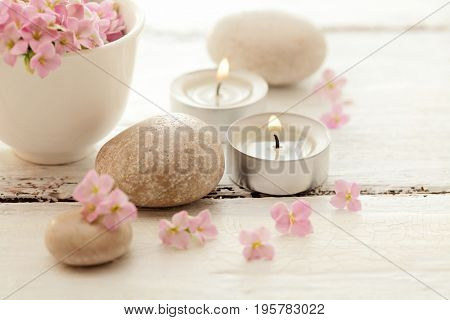 SPA still life. aromatherapy candles, pebbles and flowers