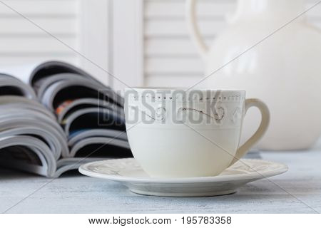 Stack Of Magazines And White Cup Of Coffee On White Background.