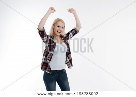 Finally done. Attractive woman smiling on camera and keeping arms upwards while standing over white background