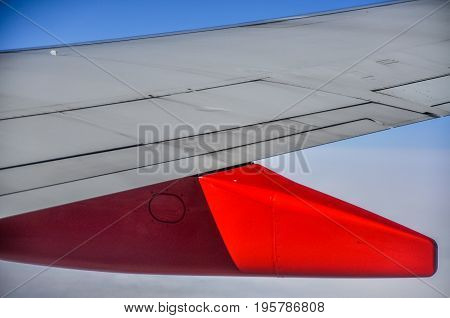 Close up of the bright red strut and wing flaps on an aircraft in mid flight in a concept of travel and transport