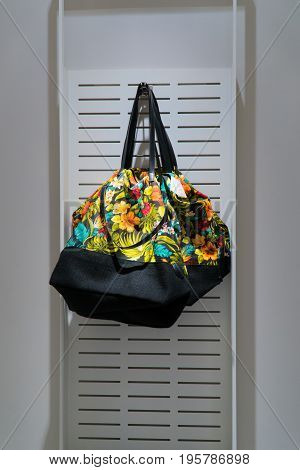 A colored bag is sold in the store. A stylish bag hangs on the wall in the store.