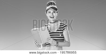 Smiling Fit Woman In Red Sun Visor On Beach With Book