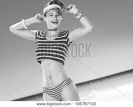 Woman On Beach With Headphones Listening To Music And Dancing