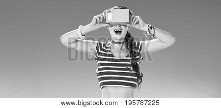 Perfect summer. smiling active woman on the seacoast wearing cardboard VR gear