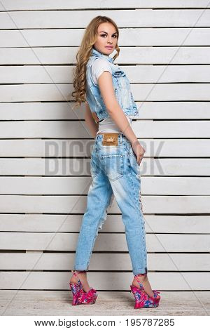 Attractive blond woman posing in blue jeans and colored shoes near wooden wall