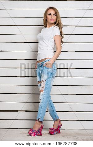 Pretty blond woman posing in blue ripped jeans and white t-shirt near wooden wall