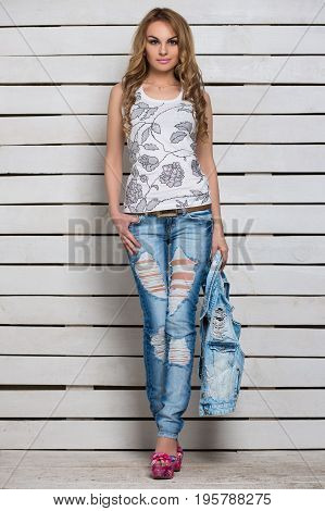 Attractive young blonde posing in blue ripped jeans and white flowered top