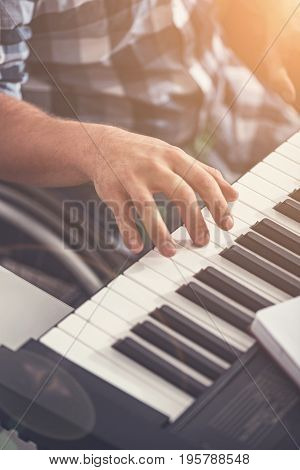 Black and white. Invalid man sitting in wheelchair touching keyboard while writing music
