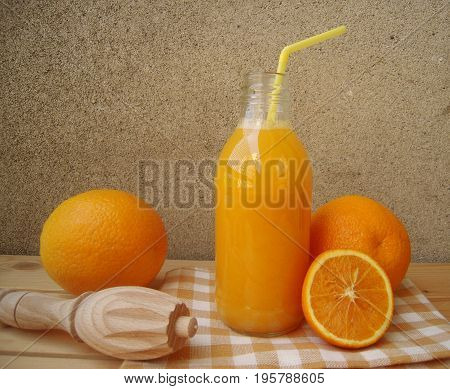 Freshly squeezed orange juice in a glass bottle with straw and juicer on a rustic table.