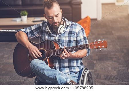 Be healthy. Serious disabled male person bowing his head while playing the guitar sitting in wheelchair