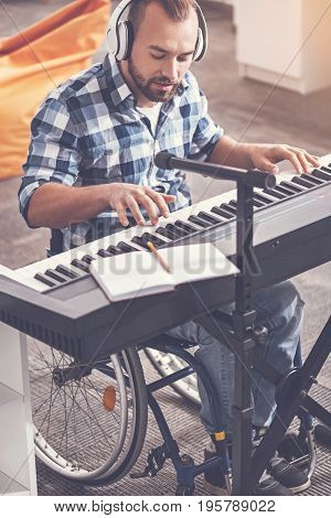 You will like it. Infatuated with music man wearing earphones looking downwards while playing the electric piano