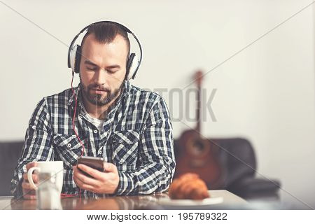 Time for relax. Delighted male person wearing headphones looking at his phone while holding white cup in right hand