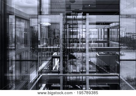 Abstract window reflections in morden office building. Contemporary corporate business architecture. Black and white, blue toned image.