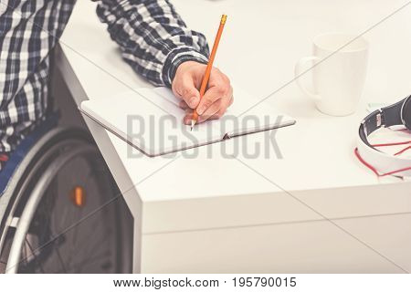 Must work. Disabled male wearing checked shirt sitting in wheelchair, making notes