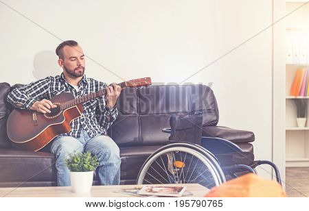I wrote it. Handsome bearded man holding the guitar putting hands on strings while controlling the process
