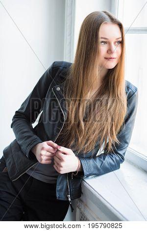Portrait of beautiful thoughtful woman posing near the window