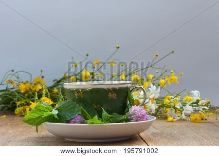 Cup And Saucer With Fresh Mint Leaves And Clover Flowers. Yellow Buttercups And Chamomiles As A Back