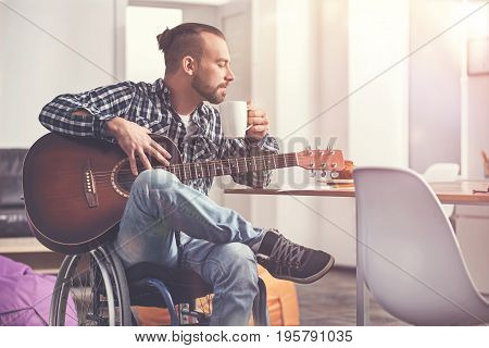 Peaceful life. Enigmatical bearded man leaning on the table, sitting on the wheelchair holding white cup with tea in left hand