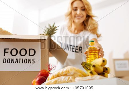 A bottle in each box. Graceful devoted sweet woman picking the appropriate foods while working pro bono and packing boxes for shipment to those in need