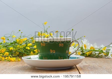 Yellow Wildflowers And Chamomiles As A Background For A Cup And Saucer. Wooden Table.