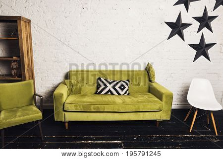 Modern living room with green couch. Scandinavian interior with sofa and chair. White wall and black wooden floor