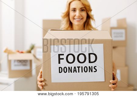 Noble intentions. Altruistic active cute woman holding a box full of food she wanting sending to those in need