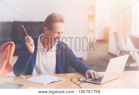 Like whta I do. Positive delighted office worker sitting at the table and using laptop while being involved in work