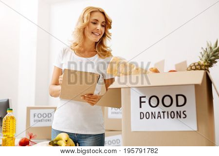 Monitoring the process. Elegant pretty motivated lady holding a list she reading and checking the foods stored in boxes in the organizations office