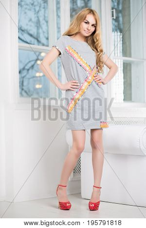 Playful blond woman posing in short gray dress near the window