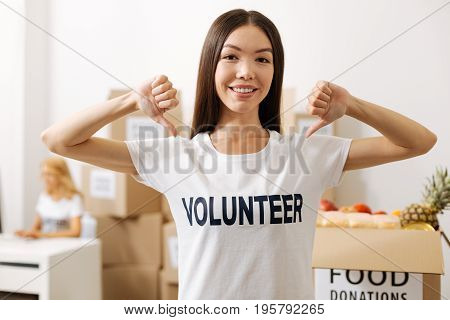 Promoting benevolence. Persistent charismatic pretty lady pointing at her shirt while encouraging everyone joining her and working pro bono