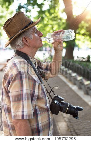 Old pensioner tourist man drinking water from bottle in park