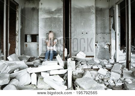 A lonely girl in a white T-shirt and jeans sits on the ruins of a ruined house. Sad expression, tragic atmosphere. Russia