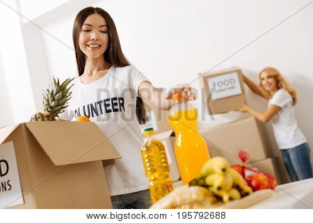 Using every bit of help. Adorable graceful committed lady packing a box with food for shipping it to those in need while working pro bono