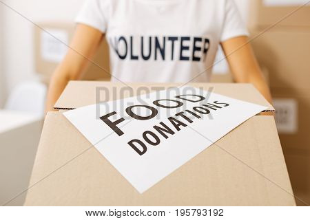 Pro bono service. Charming bright energetic woman holding a box with food supplies people donating for those in need while working as a volunteer