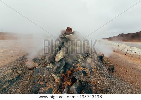 Smoking fumarole on Hverarond valley geothermal area, north Iceland, Europe. Myvaten Lake, wich is full of mudpots, steam vents, sulphur deposits, boiling springs and fumaroles.