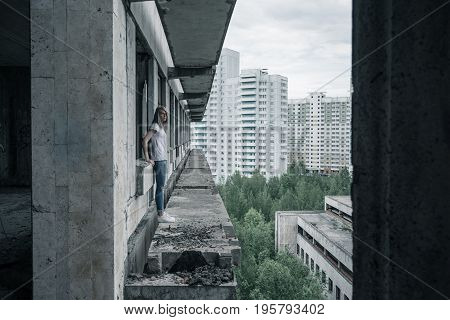 A young girl in a white T-shirt and blue jeans is standing on the edge of a ruined balcony in a ruined building early in the morning. Russia