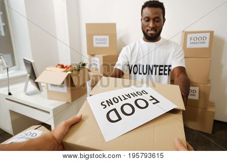Benevolent endowment. Incredible attentive young gentleman working for welfare organization and shipping supplies to poor while packing parcels in the office