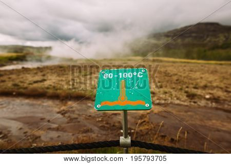 Warning sign of hot earth.Caution of high temperature on golden circle tour near big geyser geothermal area.Steaming boiling water and ground.Tourist attraction of watching geyser erupting in Iceland