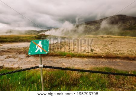 Warning sign of not crossing over rope fence.Caution of high temperature on golden circle tour near big geyser geothermal area.Steaming and boiling acid water and ground.Tourist attraction of eruption
