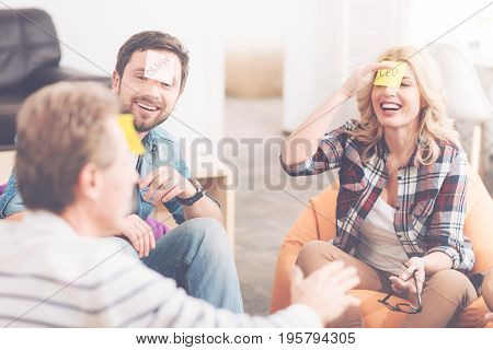 Involved in positivity. Cheerful content smiling colleagues sitting in the office and playing game with sticky notes while expressing gladness