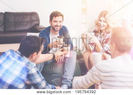 Coffee break. Cheerful delighted friends sitting in circle and talking while drinking coffee
