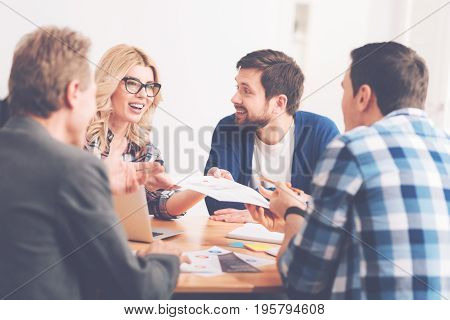 Thats a great idea. Cheerful involved business partners sitting at the table and working on the project while expressing joy