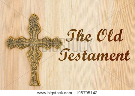 The old Testament text with a gold detailed cross on wood