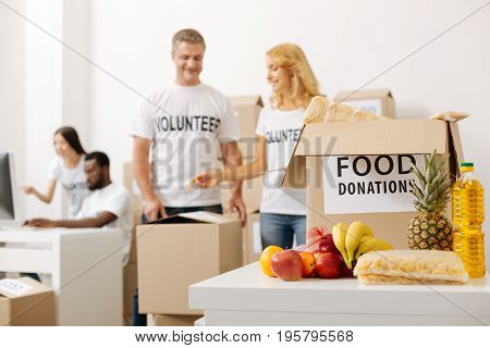 Let us have a look. Stunning devoted energetic lady managing the process of packing and asking her colleague helping her opening the package