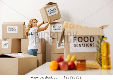 So many boxes. Vibrant clever nice lady needing another box for fitting all the food in it while preparing a shipment for those in need