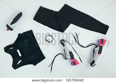 flat lay with sportswear with sneakers fitness tracker and sports bottle isolated on grey poster